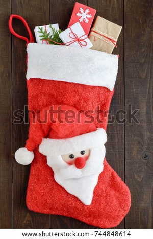 Christmas, New Year's boot for gifts with a Santa face, full of gift boxes on a dark wooden background. Theme of winter holidays.