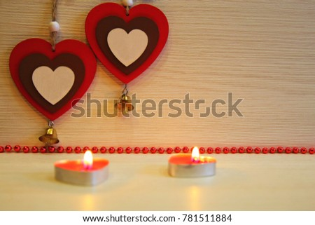 Christmas, New Year, St. Valentine's Day. Two multicolored hearts, lit candles, red beads, on a light background.