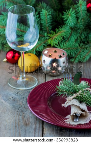 Christmas (New Year) table appointments. Fork, knife decorated thuja branches and twine bow with wine glass on wooden background - stock photo