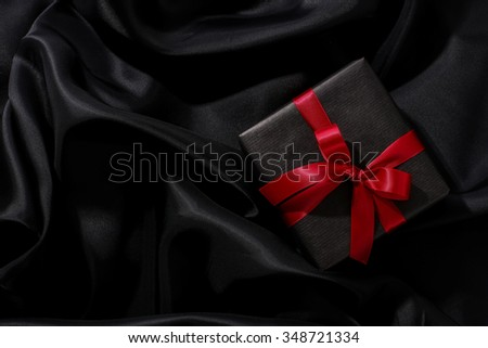 Christmas, New Year. Wrapped gift on a black background - stock photo
