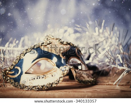 Christmas night, abstract holiday backgrounds with carnival mask over wooden desk