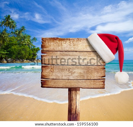 Christmas on beach. Wooden signboard with Santa's hat. - stock photo