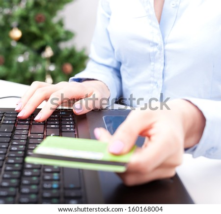 Christmas on-line shopping, woman using credit card for payment, New Year tree on background - stock photo