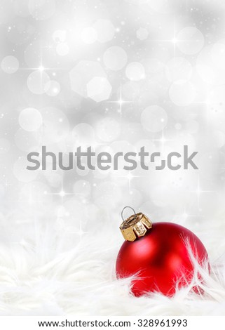 Christmas or holiday background with a red ornament against a festive, sparkling silver background