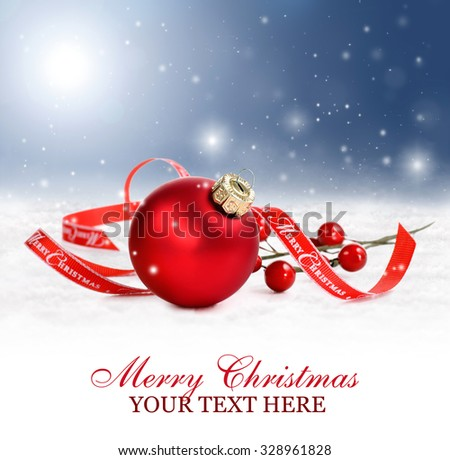 Christmas or holiday background with red ornament and merry christmas ribbon in snow. Snowflakes are falling from the sky.