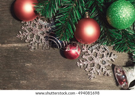 Christmas or new year background. Fir tree branch, silver jingle bells, snowflakes and christmas balls on old wooden board. Holiday concept. Free copyspace for text or images. Top view.