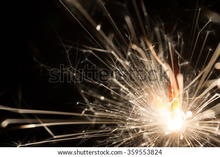Christmas or New Year celebration close-up of a burning sparkler firework on a black background - stock photo