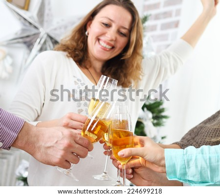 Christmas or New Year celebration. People holding glasses of champagne making a toast by the Christmas tree - stock photo