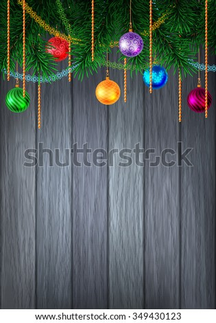 Christmas or New Year colorful greeting card with evergreen pine branch and baubles with tinsel. Decorated wood background