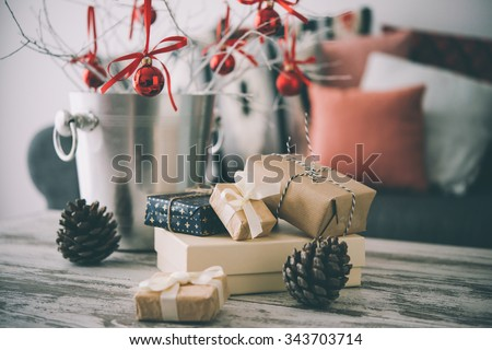Christmas or new year decoration on modern wooden coffee table. Cozy sofa with pillows on a background. Living room interior and holiday home decor concept. Toned picture - stock photo