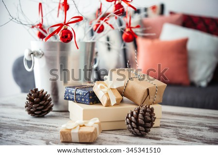 Christmas or new year decoration on modern wooden coffee table. Cozy sofa with pillows on a background. Living room interior and holiday home decor concept - stock photo