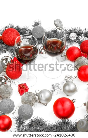 Christmas or New Year decoration with pine or fir and red ornaments balls with two glasses of wine.  Empty space or place for your text, greeting card. Black and White photo with separate red color - stock photo