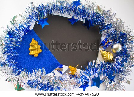Christmas or New Year flat composition for greeting card. Blue sparkling ribbon wreath. Gold fir tree ornament and blue gift. Black paper with blank page. Season background for winter holidays