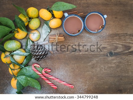 Christmas or New Year frame. Fresh mandarins with leaves, cinnamon sticks, pine cone, hot chocolate in mugs and candy canes over rustic wooden background, top view, copy space