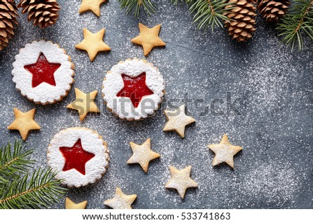 Christmas or New Year homemade ginger cookies star with strawberry jam. Traditional Austrian dessert - Linzer biscuits. Flat lay. Festive decoration. Top view. Copy space.