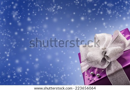 Christmas or Valentine's purple gift with silver ribbon abstract blue background - stock photo