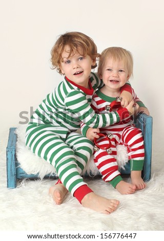 Christmas or winter themed image, children with striped pjs on bed with jingle bells
