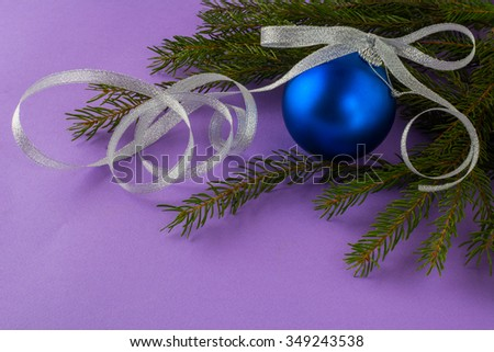 Christmas ornament deep blue ball with silver bow and fir branches on a lilac background, Christmas decoration, Merry Christmas - stock photo