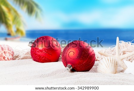 Christmas ornament on a beach,concept of a warm, tropical weather Christmas - stock photo