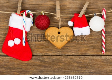 Christmas ornament - red sock gift, gingerbread heart, globes, candy cane, rope with wood hooks on old wooden background - stock photo