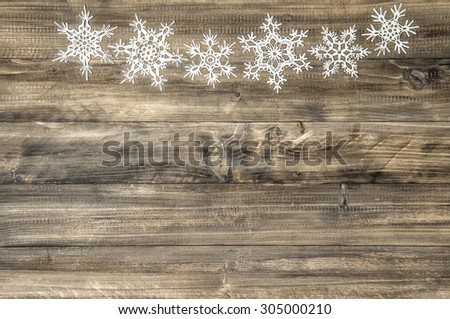 Christmas ornament white snowflakes on rustic wooden background. Festive decoration