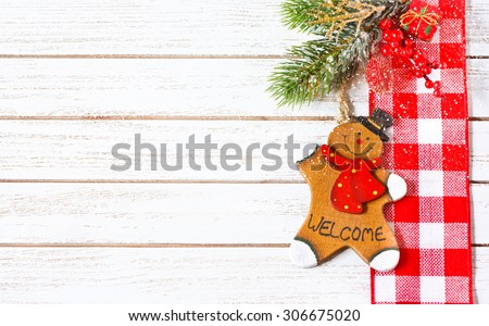 Christmas ornament with decorative cookie man hanging on christmas tree branch.