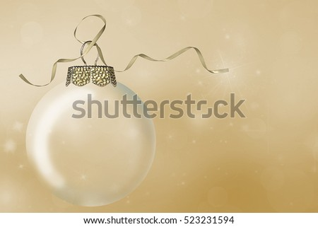 Christmas ornament with gold ribbon on sparkling golden bokeh background