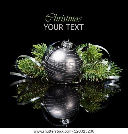 Christmas ornament with pine tree branches on a black background - stock photo