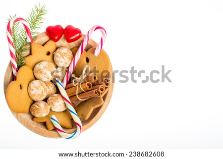 Christmas ornament - wooden bowl with gingerbread, candy cane, red hearts, cinnamon and fir branch on white background - stock photo