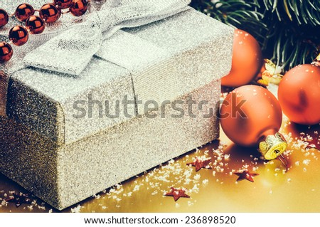Christmas ornaments and present in silver shiny box - stock photo
