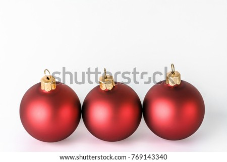 Christmas ornaments isolated on white background. Decoration on card, red shiny baubles with reflections.
