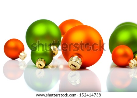 Christmas ornaments - orange and green, on a white background with copy space - stock photo