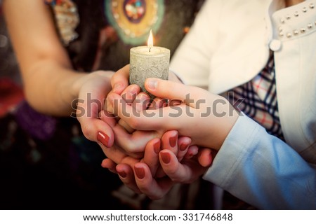 Christmas photo: hands of mother and daughter holding a candle - stock photo