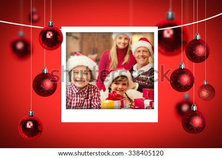 Christmas photographs against portrait of a festive family in santa hat
