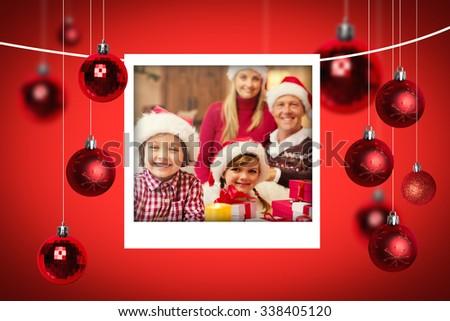 Christmas photographs against portrait of a festive family in santa hat - stock photo