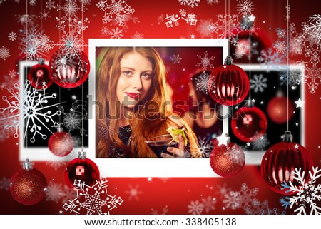 Christmas photographs against pretty redhead drinking a cocktail - stock photo