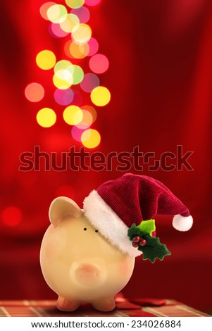 Christmas Piggy bank Santa with festive bokeh background - stock photo