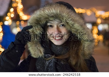 Christmas portrait of a laughing girl in a fur hat - stock photo