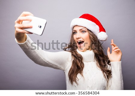 Christmas portrait of beautiful girl. Girl wearing santa claus hat. Girl smiling and making selfie on mobile phone - stock photo