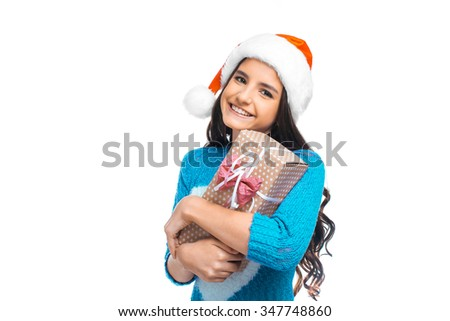 Christmas portrait of beautiful girl. Teenager wearing santa claus hat. Girl smiling, holding gift and looking at camera - stock photo