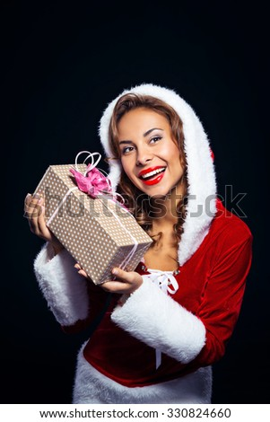 Christmas portrait of beautiful mixed-race santa girl. Young sexy brunette woman wearing santa claus clothes. Snow Maiden holding present on black background - stock photo
