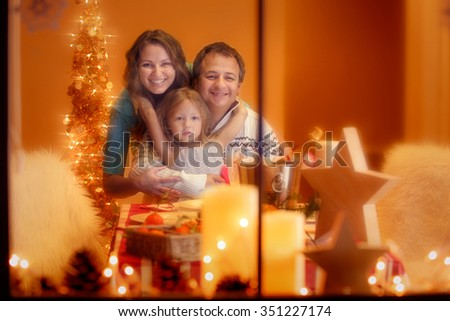 Christmas Portrait of happy family of three. Mother, father and daughter celebrating Christmas at home, looking through the window.   - stock photo