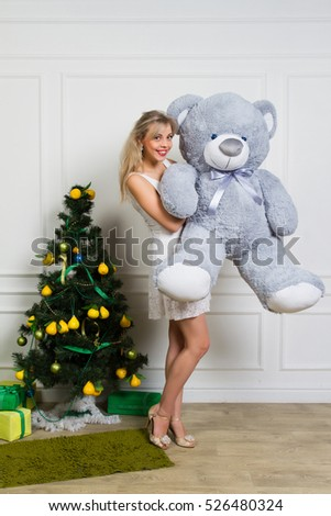 Christmas portrait of happy girl with a teddy bear in his hands in a cozy interior