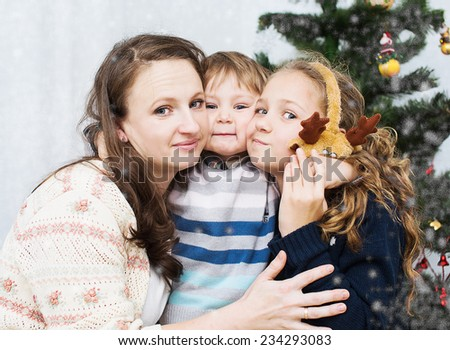 Christmas portrait of happy mother with children at home