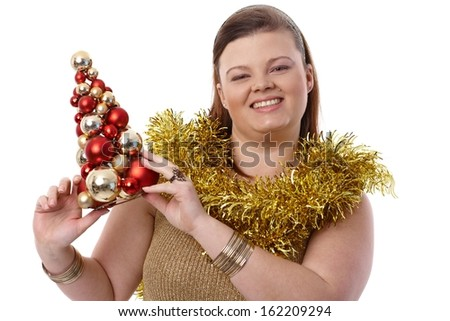 Christmas portrait of happy plump woman holding small christmas tree, smiling. - stock photo