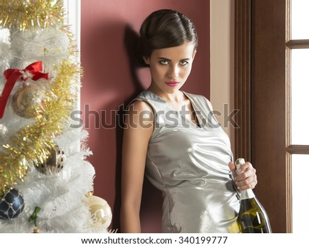 christmas portrait of pretty girl with elegant silver dress and hair-style, near decorated tree taking a bottle of champagne in the hand. xmas, new year party