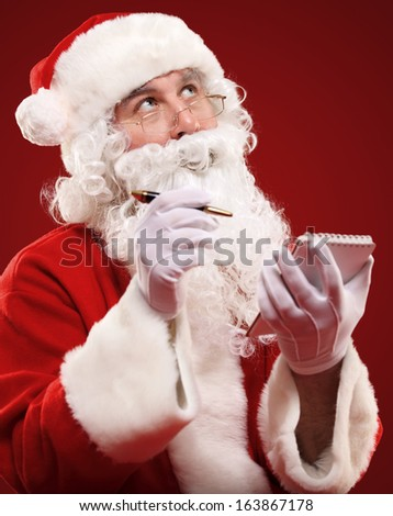 Christmas portrait of Santa Claus writing a list isolated over a red background