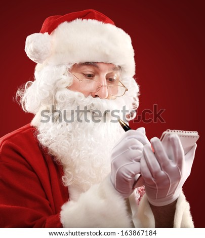 Christmas portrait of Santa Claus writing a list isolated over a red background  - stock photo