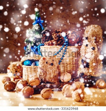 Christmas Postcard with Hand Made Toys and Presents. Basket with Cones, Fir Tree, Walnuts, Toy Animals under the Snow. Festive Mood. Selective Focus. - stock photo