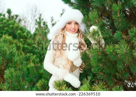 Christmas poster. Young smiling woman with fur white hat, woolen mittens, sweaters in the winter fir forest. Fir branches. - stock photo